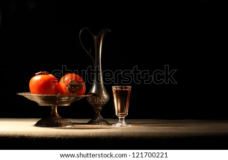 Antique vases with persimmons near glass of wine on dark background - stock photo
