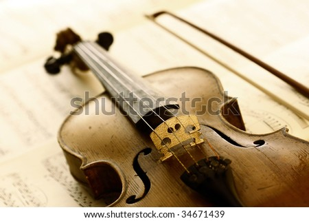 antique violin with fiddlestick - stock photo