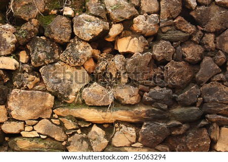 Antique wall construction made of stones. - stock photo