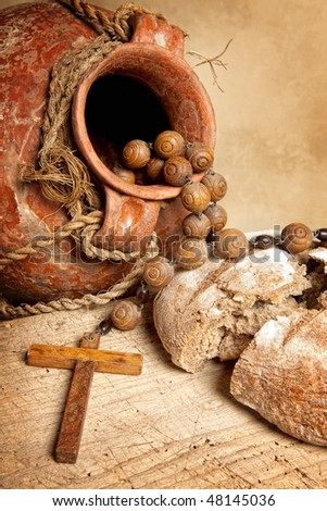 Antique wine jug, cross and rustic loaf of bread as christian symbols of faith - stock photo