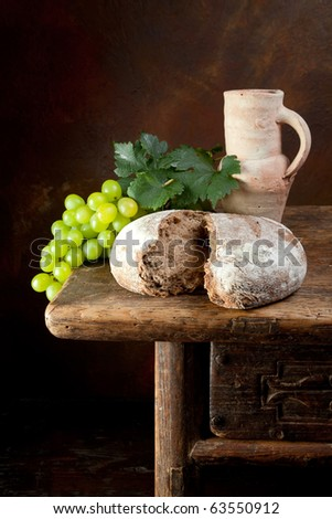 Antique wine jug with grapes and holy bread - stock photo