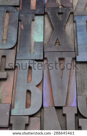antique wood letterpress printing blocks with color ink patina, random collection with L, X, V, and B letters - stock photo