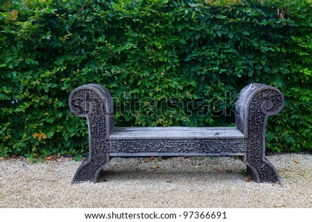 Antique wooden bench on white pebble garden and lush green leaf facade. - stock photo