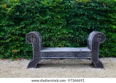 Antique wooden bench on white pebble garden and lush green leaf facade. - stock photo