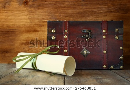 antique wooden chest with old parchment on wooden table  - stock photo