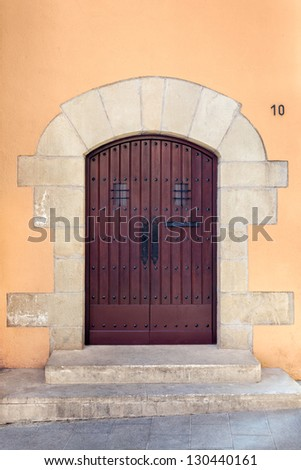 Antique wooden door with studs that hold up the planks and an arched stone frame. Shot in the Sarri�  quarter of Barcelona, where old wooden doors are still typical, specially in historical buildings. - stock photo