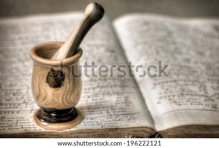 Antique wooden mortar and pestle on top of old pharmacy book - stock photo