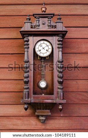 antique wooden pendulum clock hanging on wooden wall - stock photo