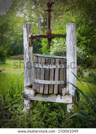 Antique wooden wine press left in garden surrounded by flowers - stock photo