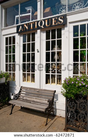 Antiques sign hangs above and a weathered bench sits below the windows of a vintage goods store in a small town. - stock photo