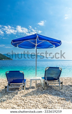 Antisamos beach Kefalonia island, Greece. Parasols and sunbeds on a beautiful beach in Greece. - stock photo