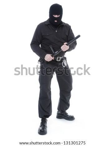 Antiterrorist police guy wearing black uniform and black mask holding firmly police club in both hands ready for action, shot on white
