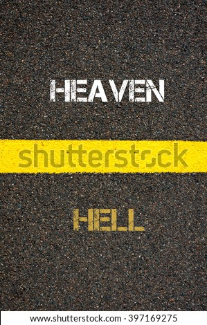 Antonym decision concept of HELL versus HEAVEN written over tarmac, road marking yellow paint separating line between words