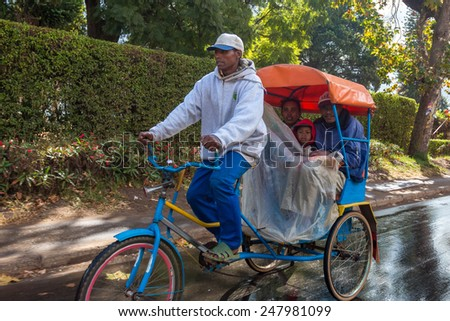 Antsirabe, Madagascar - May 23: - Malagasy people hire a Pousse-Pousse (rickshaw) for their daily commute on May 23, 2014 in Antsirabe, Madagascar. - stock photo