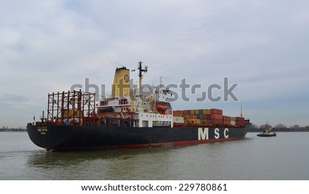 ANTWERP, BELGIUM, FEBRUARY 18, 2014: Cargo ship loaded with dozens of containers is entering port of antwerp.