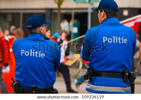 ANTWERP, BELGIUM - MAY 1: Two Flemish Policemen watch over marchers and keep the peace at the annual May Day Parade on May 1, 2010 in Antwerp, Belgium - stock photo