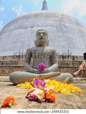 Anuradhapura, sitting Budha with flowers and dagoba Ruvanvelisaya, Sri Lanka - stock photo