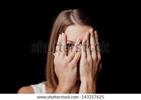 Anxiety - a conceptual image of a woman covering her face with her hands and peering out with one eye between her fingers on a dark studio background - stock photo