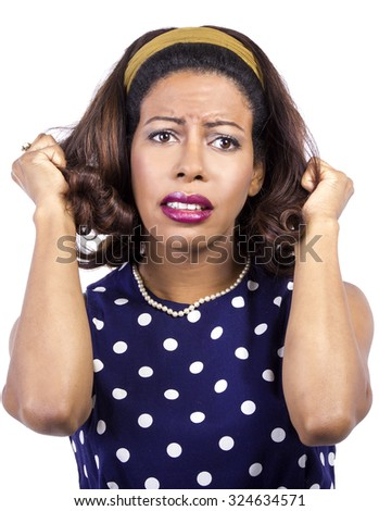 Anxious black female wearing retro fashion style polka dot dress.  She is fed up and pulling her hair. - stock photo