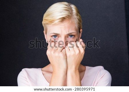 Anxious blonde woman looking at camera on black background - stock photo