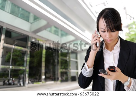 Anxious business woman phone someone and reading SMS outside of office. - stock photo