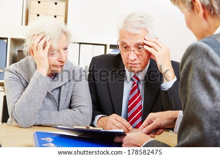 Anxious elderly senior couple worring about financial security at consultation - stock photo