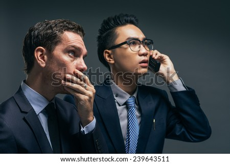 Anxious financial brokers looking at the electronic stock exchange board - stock photo