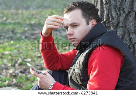 anxious man holding a mobile phone - stock photo