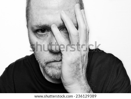 Anxious man worrying about something with his hand on his face on white background. - stock photo