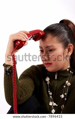 Anxious woman holding a telephone on a white background