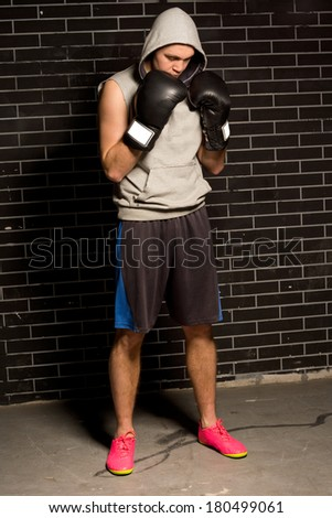 Anxious young boxer standing waiting for his match with his gloved fists raised to his chin as he stares down at the floor in front of a brick wall - stock photo