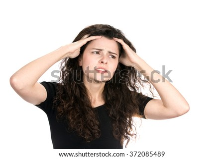 Anxious young businesswoman runs her fingers through her hair as she worries and stresses about her situation. - stock photo