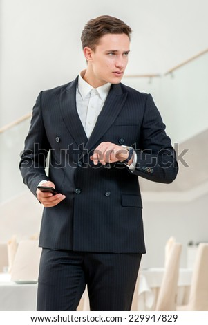 Any delay in the appointment. Confident and successful businessman in a strict dress standing in an office and talking on mobile phone while looking at his watch on his arm - stock photo