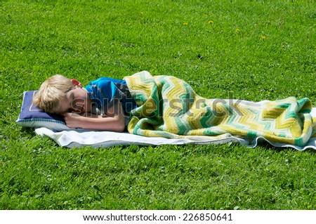 Anytime is the right time for a nap so the little boy lays down on the grass and covers himself with a blanket - stock photo