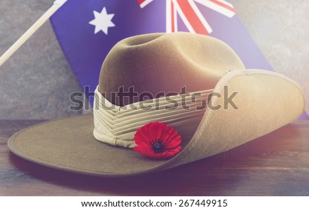 Anzac army slouch hat with Australian Flag on vintage wood background with applied retro vintage filters and added light effects. - stock photo