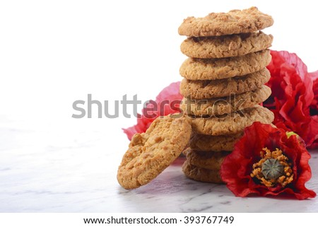 ANZAC Day, April 25, traditional Anzac biscuits on white marble table with red poppies, with copy sapce.   - stock photo