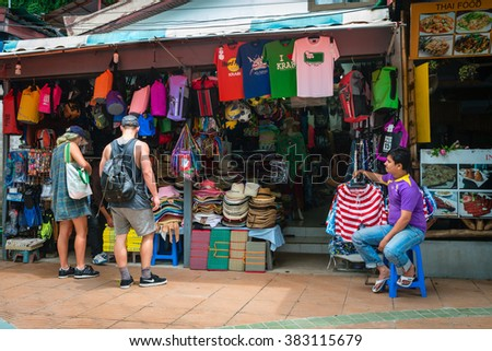 AO NANG, KRABI, THAILAND - 15 OCT 2014: Retail market stall selling souvenirs, hats, colorful balls and bags outside and the shop keeper sitting on a stool. - stock photo