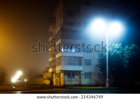 Apartment block on empty night city street covered with fog, blurred city lights glow through misty haze - stock photo