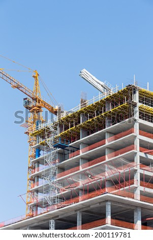 Apartment building construction site with cranes against blue sky