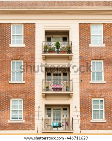 Apartment building exterior wall red brick symmetrical architecture with windows and balconies in three.