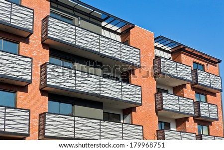 Apartment building with exterior balconies located in the city.  - stock photo