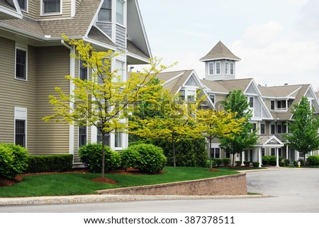 apartment building with spring tree landscape - stock photo