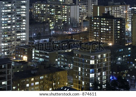 Apartment buildings at night with lights on. - stock photo