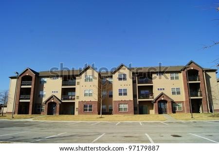 Apartment Complex Building on Parking Lot - stock photo