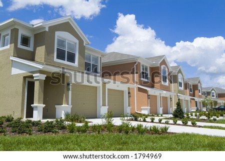 Apartment condos all coloful under bright blue sky and clounds - stock photo