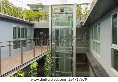 apartment interior with walkway bridge and glass lift. - stock photo