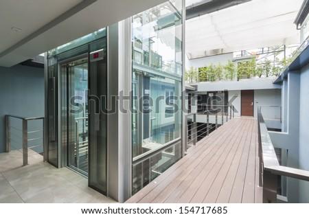 apartment interior with walkway bridge and glass lift opened. - stock photo