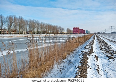 Apartments along a frozen canal in winter - stock photo