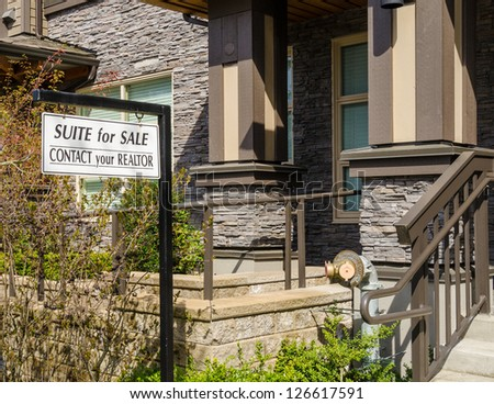 Apartments For Sale Real Estate Sign in Front of New House. - stock photo