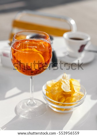 Aperol spritz cocktail with olive and orange piece as it can be served in Venice, Italy.